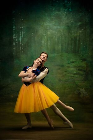 Young ballet dancers as a Snow Whites characters in forest. Flexible caucasian artists dance like character of fairytail in bright clothes. Adorable and elegance story in motion and dancing, artwork. 写真素材