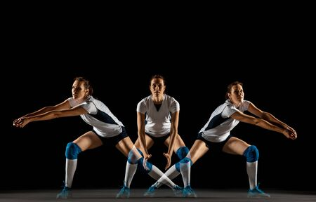 Young female volleyball player isolated on black studio background. Woman in sports equipment and shoes or sneakers training and practicing. Concept of sport, healthy lifestyle, motion and movement.