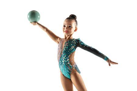 Mała dziewczynka elastyczne na białym tle na tle białego studia. Mała modelka jako artystka gimnastyki rytmicznej w jasnym trykocie. Łaska w ruchu, akcji i sporcie. Wykonywanie ćwiczeń z piłką.
