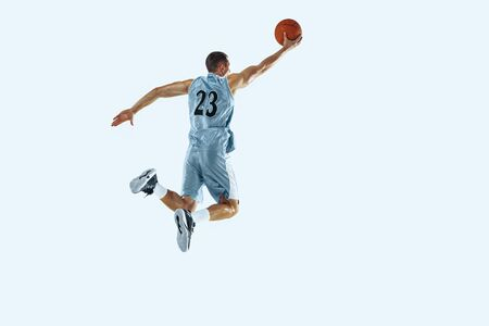 High flight. Young caucasian basketball player of team in action, motion in jump isolated on white background. Concept of sport, movement, energy and dynamic, healthy lifestyle. Training, practicing. Reklamní fotografie