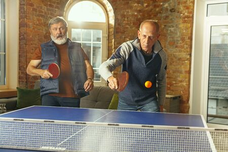 Senior men playing table tennis in workplace, having fun. Friends in casual clothes play table tennis together at sunny day. Concept of leisure activity, sport, friendship, teambuilding, teamwork.