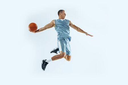 High flight. Young caucasian basketball player of team in action, motion in jump isolated on white background. Concept of sport, movement, energy and dynamic, healthy lifestyle. Training, practicing.