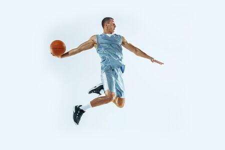 Hoher Flug. Junge kaukasische Basketballspieler des Teams in Aktion, Bewegung im Sprung isoliert auf weißem Hintergrund. Konzept von Sport, Bewegung, Energie und dynamischem, gesundem Lebensstil. Trainieren, üben.