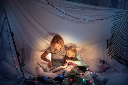 Mother and daughter sitting in a teepee, reading stories with the flashlight in dark room with toys and pillows. Caucasian models. Home comfort, family, love, Christmas holidays, storytelling time. Standard-Bild