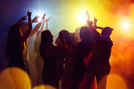 Acting. A crowd of people in silhouette raises their hands on dancefloor on neon light background. Night life, club, music, dance, motion, youth. Yellow-blue colors and moving girls and boys.