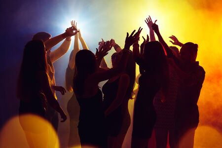 Wild. A crowd of people in silhouette raises their hands on dancefloor on neon light background. Night life, club, music, dance, motion, youth. Yellow-blue colors and moving girls and boys.