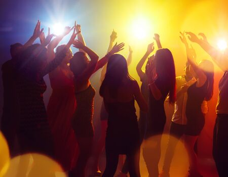 Brightness. A crowd of people in silhouette raises their hands on dancefloor on neon light background. Night life, club, music, dance, motion, youth. Yellow-blue colors and moving girls and boys.