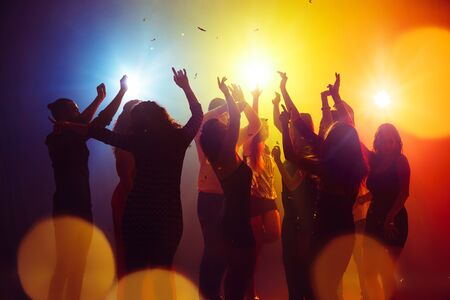 Confetti. A crowd of people in silhouette raises their hands on dancefloor on neon light background. Night life, club, music, dance, motion, youth. Yellow-blue colors and moving girls and boys.