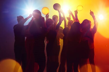 Vibes. A crowd of people in silhouette raises their hands on dancefloor on neon light background. Night life, club, music, dance, motion, youth. Yellow-blue colors and moving girls and boys. Banco de Imagens