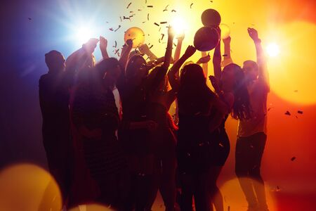 Summer nights. A crowd of people in silhouette raises their hands on dancefloor on neon light background. Night life, club, music, dance, motion, youth. Yellow-blue colors and moving girls and boys.
