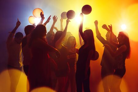 Happiness. A crowd of people in silhouette raises their hands on dancefloor on neon light background. Night life, club, music, dance, motion, youth. Yellow-blue colors and moving girls and boys.