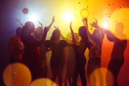 Emotions. A crowd of people in silhouette raises their hands on dancefloor on neon light background. Night life, club, music, dance, motion, youth. Yellow-blue colors and moving girls and boys. Banco de Imagens