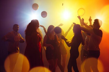 Feelings. A crowd of people in silhouette raises their hands on dancefloor on neon light background. Night life, club, music, dance, motion, youth. Yellow-blue colors and moving girls and boys. Banco de Imagens