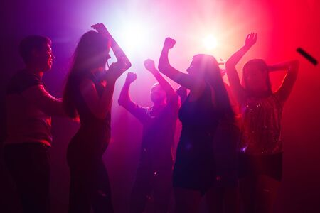 Jam session. A crowd of people in silhouette raises their hands on dancefloor on neon light background. Night life, club, music, dance, motion, youth. Purple-pink colors and moving girls and boys.