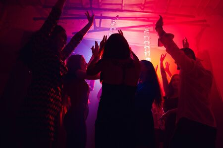 Until the morning. A crowd of people in silhouette raises their hands on dancefloor on neon light background. Night life, club, music, dance, motion, youth. Purple-pink colors and moving girls and boys. Banco de Imagens