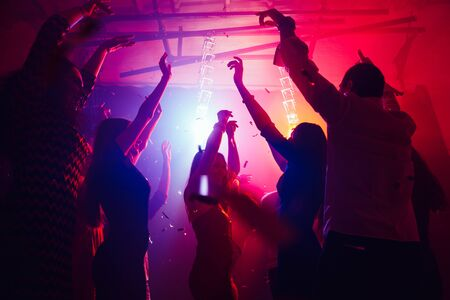 Leisure. A crowd of people in silhouette raises their hands on dancefloor on neon light background. Night life, club, music, dance, motion, youth. Purple-pink colors and moving girls and boys.