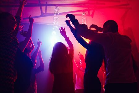 Cheers. A crowd of people in silhouette raises their hands on dancefloor on neon light background. Night life, club, music, dance, motion, youth. Purple-pink colors and moving girls and boys. Banco de Imagens