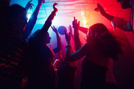 Una multitud de personas en silueta levanta sus manos en la pista de baile sobre fondo de luz de neón. Vida nocturna, club, música, baile, movimiento, juventud. Colores violeta-rosa y niñas y niños en movimiento. Foto de archivo