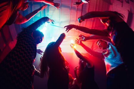 Remember. A crowd of people in silhouette raises their hands on dancefloor on neon light background. Night life, club, music, dance, motion, youth. Purple-pink colors and moving girls and boys. Banco de Imagens