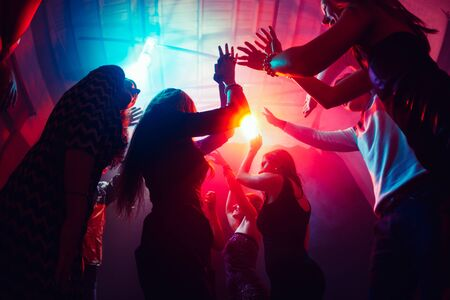 Jusqu'au lever du soleil. Une foule de personnes en silhouette lève les mains sur la piste de danse sur fond néon. Vie nocturne, club, musique, danse, mouvement, jeunesse. Des couleurs rose-violet et des filles et des garçons émouvants.