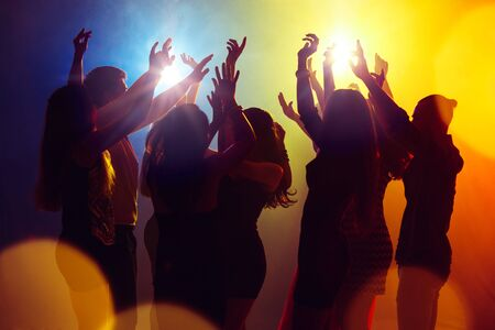 Dreams. A crowd of people in silhouette raises their hands on dancefloor on neon light background. Night life, club, music, dance, motion, youth. Yellow-blue colors and moving girls and boys. Banco de Imagens