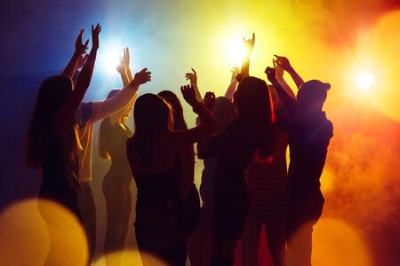 Action. A crowd of people in silhouette raises their hands on dancefloor on neon light background. Night life, club, music, dance, motion, youth. Yellow-blue colors and moving girls and boys. Stock Photo