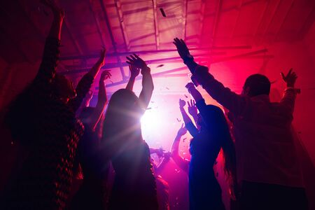 New Years. A crowd of people in silhouette raises their hands on dancefloor on neon light background. Night life, club, music, dance, motion, youth. Purple-pink colors and moving girls and boys.