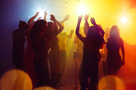Holidays. A crowd of people in silhouette raises their hands on dancefloor on neon light background. Night life, club, music, dance, motion, youth. Yellow-blue colors and moving girls and boys. Imagens