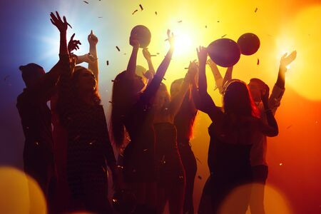 Corporate. A crowd of people in silhouette raises their hands on dancefloor on neon light background. Night life, club, music, dance, motion, youth. Yellow-blue colors and moving girls and boys.