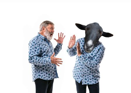 Portrait of senior man arguing with himself as a donkey on white studio background. Concept of human emotions, expression, mental issues, internal conflict, split personality. Copyspace. Scream.