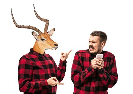 Portrait of man arguing with himself as a deer on white studio background. Concept of human emotions, expression, mental issues, internal conflict, split personality. Copyspace. Scream.