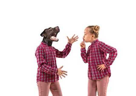 Young handsome girl arguing with herself as a dog on white studio background. Concept of human emotions, expression, mental issues, internal conflict, split personality. Agressive talking. Stockfoto