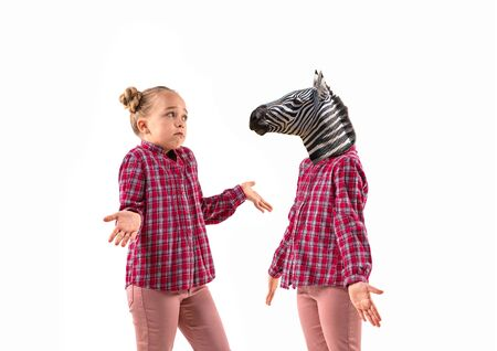 Young handsome girl arguing with herself as a zebra on white studio background. Concept of human emotions, expression, mental issues, internal conflict, split personality. Agressive talking. Reklamní fotografie