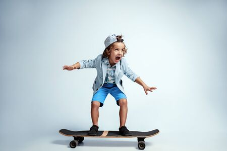 Bastante joven en patineta en ropa casual sobre fondo blanco de estudio. Montar y se ve feliz. Niño en edad preescolar masculino caucásico con brillantes emociones faciales. Infancia, expresión, diversión. Foto de archivo