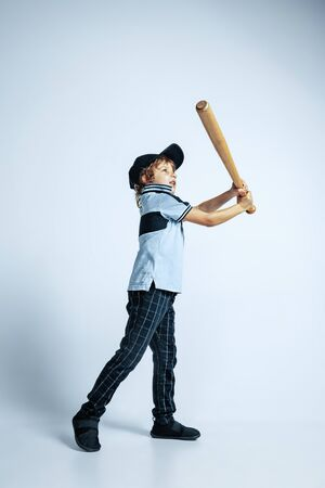 Pretty young curly boy in casual clothes on white studio background. Confident and cool with sport bat. Caucasian male preschooler with bright facial emotions. Childhood, expression, having fun. 免版税图像