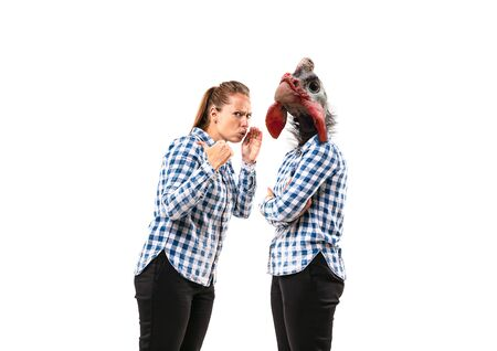 Portrait of young woman arguing with herself as a chicken on white studio background. Concept of human emotions, expression, mental issues, internal conflict, split personality. Negative space.