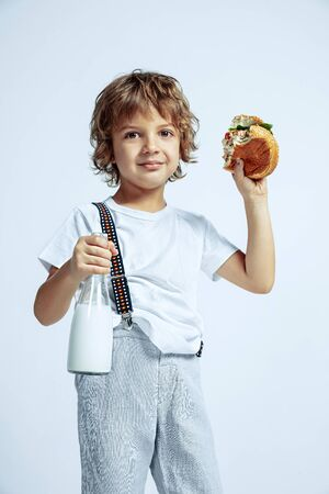 Pretty young curly boy in casual clothes on white studio background. Eating burger with milk bottle. Caucasian male preschooler with bright facial emotions. Childhood, expression, fun, fast food.