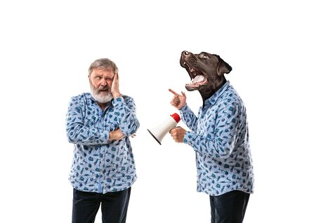 Portrait of senior man arguing with himself as a dog on white studio background. Concept of human emotions, expression, mental issues, internal conflict, split personality. Copyspace. Scream. Foto de archivo