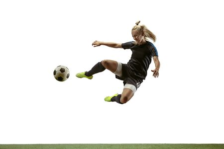 Young female soccer or football player with long hair in sportwear and boots kicking ball for the goal in jump on white background. Concept of healthy lifestyle, professional sport, motion, movement.