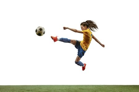 Young female soccer or football player with long hair in sportwear and boots kicking ball for the goal in jump on white background. Concept of healthy lifestyle, professional sport, motion, movement. Imagens