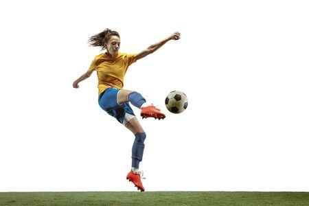 Giovane calciatore o calciatore femminile con capelli lunghi in abbigliamento sportivo e stivali che danno dei calci alla palla per l'obiettivo nel salto su fondo bianco. Concetto di stile di vita sano, sport professionistico, movimento, movimento. Archivio Fotografico