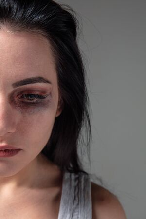 Woman in fear of domestic abuse and violence, concept of female rights. Caucasian brunette woman on grey background looks upset, sad, depressed being victim of man or husband. Has bruises, hematomas. Stock fotó