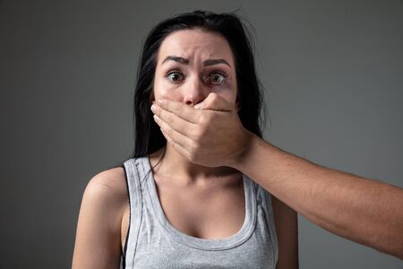 Woman in fear of domestic abuse and violence, concept of female rights. Stop agression. Caucasian woman on grey pressured, depressed, screaming being victim of man or husband. Has bruises, hematomas. Stock Photo