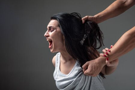 Woman in fear of domestic abuse and violence, concept of female rights. Stop agression. Caucasian woman on grey pressured, depressed, screaming being victim of man or husband. Has bruises, hematomas. 스톡 콘텐츠