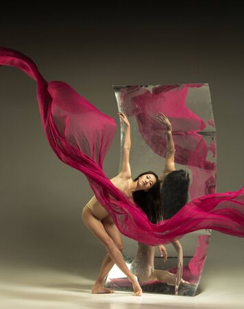 Dance with fire. Modern ballet dancer on brown background with mirror. Illusion reflections on surface. Magic of flexibility, motion with fabric. Concept of creative art dancing, action, inspiring. Imagens