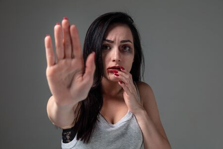 Woman in fear of domestic abuse and violence, concept of female rights. Stop agression. Caucasian woman on grey looks upset, sad, depressed being victim of man or husband. Has bruises, hematomas. 스톡 콘텐츠 - 133752277