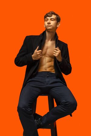 Portrait of a handsome young man isolated on orange studio background. Beautiful male model in casual clothes on high wooden chair. Beauty, fashion, facial expression, human emotions. Looks confident. Zdjęcie Seryjne
