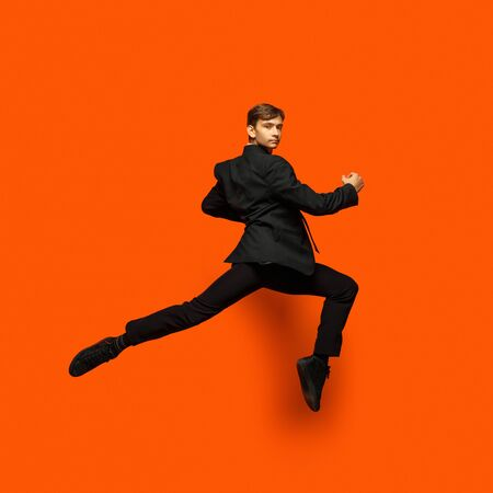 Man in casual office style clothes jumping and dancing isolated on bright orange background. Business, start-up, open-space, inspiration concept. Flexible ballet dance. Hurrying up, drinking coffee. Zdjęcie Seryjne