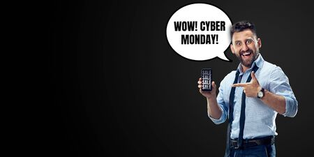 Portrait of man with speech bubble on black studio background. Copyspace for your advertising. Black friday, cyber monday, sales, money and cash, online purchases and payments. Shows phone screen.