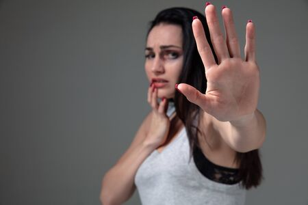 Woman in fear of domestic abuse and violence, concept of female rights. Stop agression. Caucasian woman on grey looks upset, sad, depressed being victim of man or husband. Has bruises, hematomas. 스톡 콘텐츠